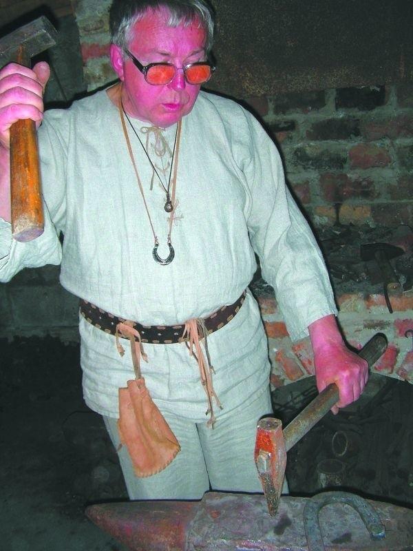 Stanisław Mierzwiński, odziany w płócienne gatki i koszulinę, prezentuje umiejętności kowalskie
