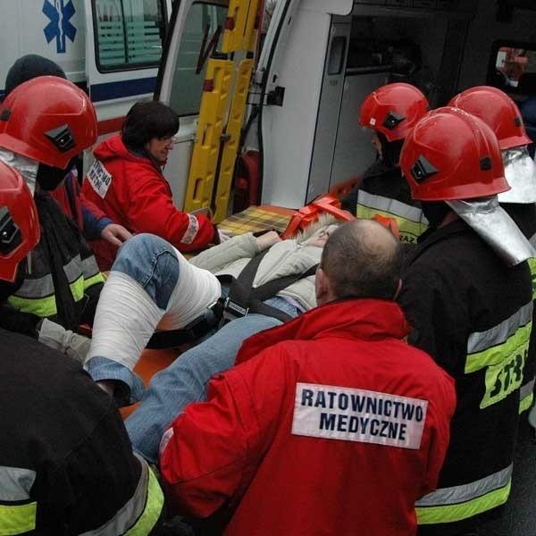 Strażacy niosą do karetki jedną z ofiar wypadku.