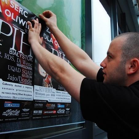 Bartek Pabisiak wraz z kolegami rozwiesza plakaty informujące o koncercie.
