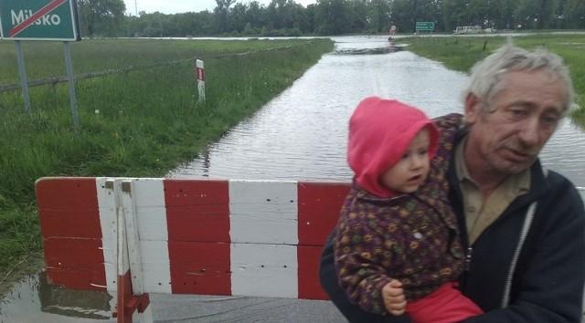 Edward Żukowski z roczną wnuczką Dominiką stoją na zalanej drodze