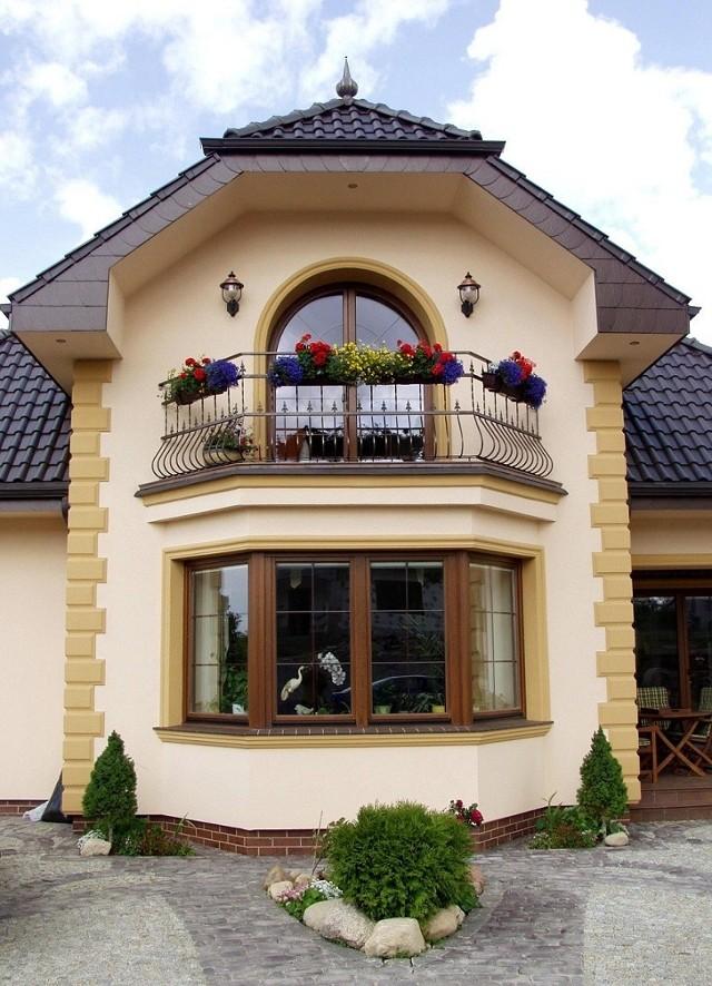 Dom z oknami drewnianymiStylowe, drewniane ramy stanowią doskonałą aranżację do obecnie budowanych domów jednorodzinnych stylizowanych na architekturę rustykalną czy dworkową.