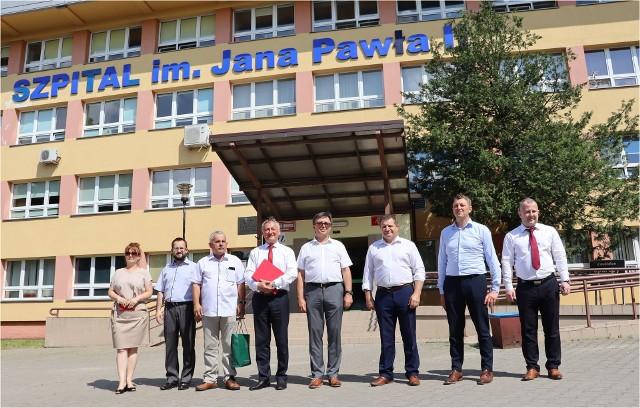 Przed budynkiem szpitala stoją od lewej: 2 Członków Zarządu Powiatu, Przewodniczący Rady Powiatu, Wojewoda Świętokrzyski, Starosta Włoszczowski, Radny Sejmiku Województwa, Dyrektor ZOZ, Wicestarosta.