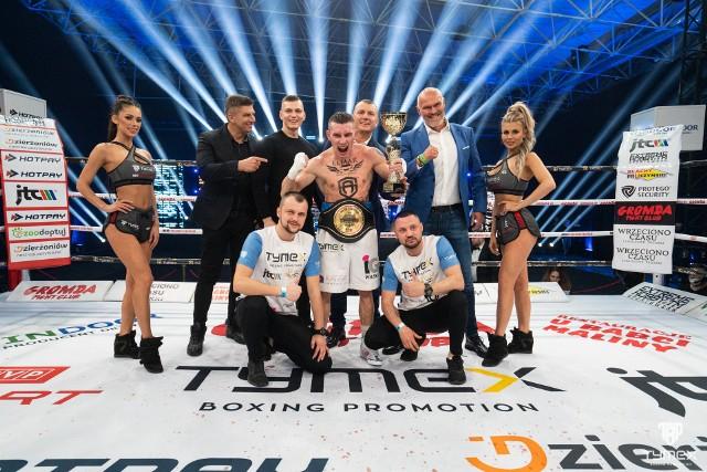 Dawid Wrzesiński cieszy się z wygranej walki wieczoru razem ze swoimi trenerami, promotorami i sponsorami
