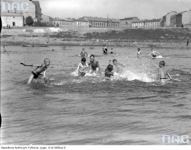 Plaża na Wisłą w Krakowie. Dzieci bawiące sie w wodzie.