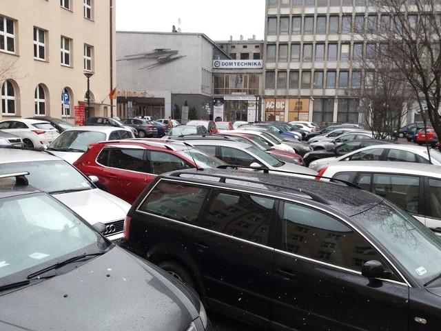 Parking obok Urzędu Miasta Łodzi pęka w szwach. Parkuje na nim więcej aut, niż jest miejsc parkingowych.