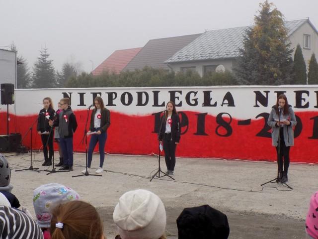 """Z okazji setnej rocznicy odzyskania niepodległości młodzież z Zespołu Szkół imienia Marii Skłodowskiej-Curie wykonała mural niepodległościowy będący podziękowaniem dla bohaterów narodowych i wyrazem szacunku  dla  Ojczyzny. W piątek, 9 listopada, nastąpiło uroczyste odsłonięcie muralu. WIĘCEJ ZDJĘĆ Z UROCZYSTOŚCI NA KOLEJNYCH SLAJDACH-  Ojczyzna, to nie tylko kawałek ziemi ojczystej, to także język, religia, obyczaj  i dorobek minionych pokoleń. Choć przez 123 lata kraj nie istniał na mapie, żył jednak naród i jego kultura. Polacy nieustannie szukali sposobu, który miał ich doprowadzić do niepodległości. Wreszcie nadszedł upragniony dzień 11 listopada 1918 roku i nasza ojczyzna znowu była niepodległa – mówił Marcin Stańczyk, dyrektor Zespołu Szkół imienia Skłodowskiej w Ożarowie do swoich uczniów, ale także do seniorów z klubu """"Vigor"""" i podopiecznych żłobka. Po tych słowach odsłonięto niepodległościowy mural. Malowidło przedstawia orła, sylwetki żołnierzy, portret Józefa Piłsudskiego, barwy narodowe, a także napis """"Niepodległa-niepokorna"""" O godzinie 11.11 cała społeczność szkolna odśpiewała hymn w ramach akcji organizowanej w całym kraju przez ministerstwo oświaty. Młodzież  z Gimnazjum i Szkoły Podstawowej """"u Skłodowskiej"""", uczniowie z zespołu Szkół w Ożarowie wypuścili także 100 białych i czerwonych balonów, które pofrunęły zamglone tego dnia niebo,  by upamiętnić odzyskanie niepodległości. ZOBACZ TAKŻE: FLESZ 12 LISTOPADA WOLNE"""