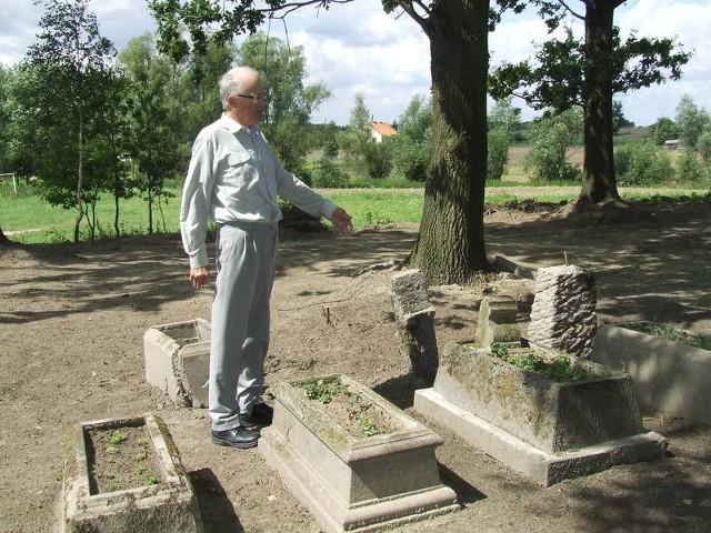 Sołtys Józef Łepek wskazuje miejsca na cmentarzu, które zostały wykoszone i uprzątnięte
