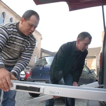 Waldemar Binder i Mariusz Płaksa składają podest do wjazdu dla osób na wózkach inwalidzkich, który zamontowano w aucie