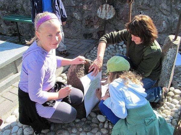Dzieci z Niepublicznej Szkoły Podstawowej i Elżbieta Stelmaszuk ze Stowarzyszenia Przyjaciół Niewodnicy odnawiają stare groby