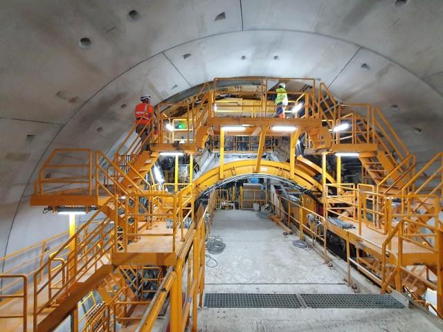 """Wydrążono już 742 metry tunelu w Świnoujściu, tym samym osiągnięto połowę długości tunelu drążonego. Maszyna drążąca TBM (ang. Tunnel Boring Machine) """"Wyspiarka"""" ułożyła 417 pierścieni obudowy i z każdym dniem zbliża się do brzegu cieśniny Świna od strony wyspy Wolin. Jesienią drążenie tunelu powinno się zakończyć. Wówczas rozpoczną się dalsze prace związane z wykończeniem tunelu. Na wrzesień przyszłego roku, zgodnie z kontraktem, przewidziano zakończenie prac.Wszystkie elementy obudowy tunelu wykonaneMaszyna TBM zarówno drąży tunel, usuwając równocześnie urobek, jak i wykonuje obudowę tunelu z prefabrykowanych elementów – tubingów. Na każdy pierścień tunelu składa się osiem takich elementów, które powstają w specjalnie wykonanym zakładzie prefabrykacji. Wszystkie 6280 tubingi zostały już wykonane, część z nich zamontowano w tunelu, a pozostałe oczekują na swoją kolej na placach składowych. Teraz w zakładzie prefabrykacji będą powstawały elementy wewnętrznych konstrukcji tunelu.Pozostałe pracePrzewiercenie się z wyspy Uznam na wyspę Wolin nie będzie oznaczało końca prac. Tunel ma przekrój kolisty, tak jak tarcza maszyny TBM. Aby mogły się nim poruszać pojazdy, trzeba będzie wykonać płytę, na której będzie zlokalizowana jezdnia. Pod nią zostanie umieszczona galeria ewakuacyjna wraz z większością instalacji tunelu. Ważnym elementem będą również wyjścia awaryjne do galerii ewakuacyjnej wymagające przebicia się poza obudowę tunelu. Wykonane zostaną również systemy wentylacji, przeciwpożarowe, zarządzania ruchem i monitoringu. Tunel połączy wyspy Uznam i WolinCałkowita długość inwestycji będzie wynosić 3,4 km. Zasadnicza jej część, czyli tunel drążony pod Świną, który połączy wyspy Uznam i Wolin, będzie miał długość 1,48 km. Tunel będzie jednorurowy i powstanie w nim dwupasowa jezdnia. Dzięki tej inwestycji Świnoujście zostanie w sposób stały skomunikowane z resztą Polski. Obecnie komunikację zapewniają przeprawy promowe, które mają mocno ograniczoną przepustowość i są z"""