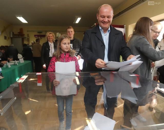 Piotr Krzystek przy urnie wyborczej.