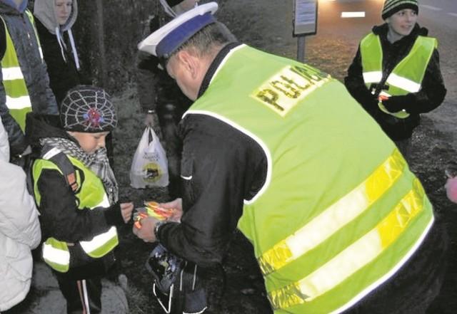 Policjanci w ramach prowadzonych akcji wręczają kamizelki oraz elementy odblaskowe idącym do szkoły dzieciom
