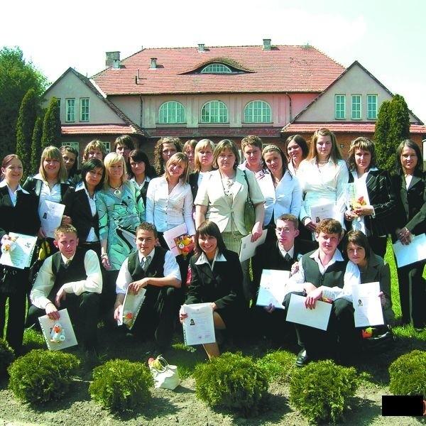 Współcześni absolwenci, jak za dawnych czasów, fotografują się na pamiątkę na tle budynku starej szkoły