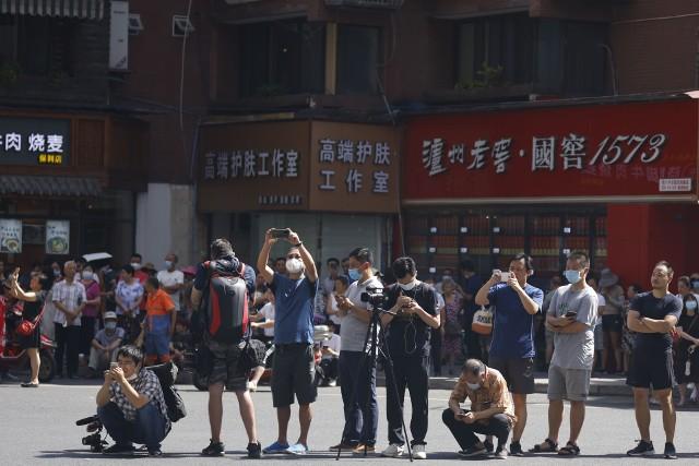 Mieszkańcy i dziennikarze robią zdjęcia w momencie, kiedy chińskie służby wkraczały w poniedziałek na teren opuszczonego konsulatu USA w Chengdu