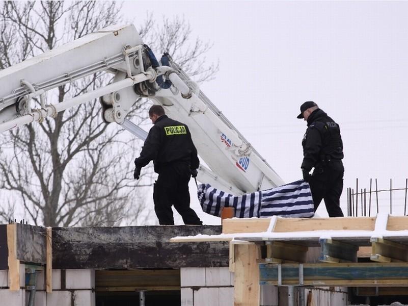 Policjanci wynoszą ciało robotnika. Do zdarzenia doszło 13 lutego 2010 roku.