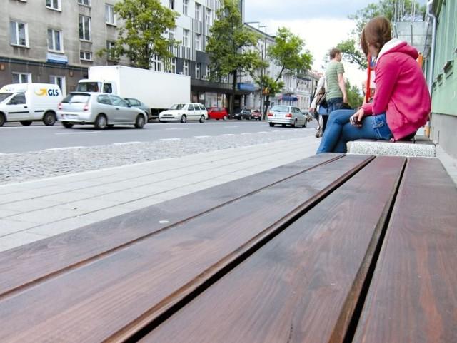 Nowe betonowo–drewniane ławki zostały wkomponowane w przestrzeń odnowionego budynku