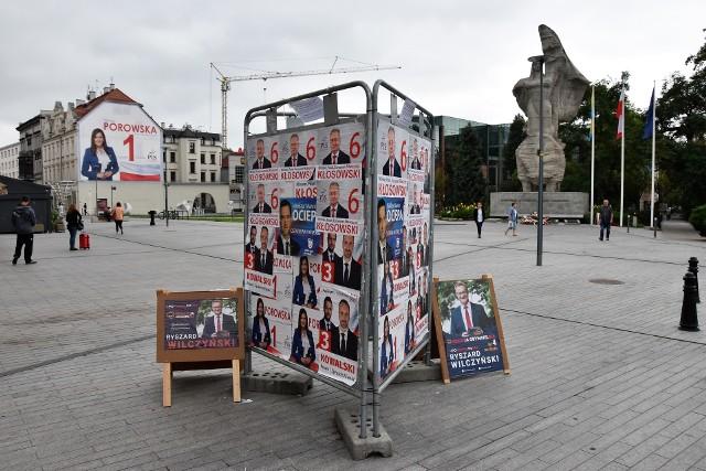 """Kandydaci PiS zaklejają się nawzajem na stojaku na ul. Krakowskiej. Ryszard Wilczyński z KO wystawił swoje """"potykacze"""" obok. MZD informuje, że bez pozwolenia."""