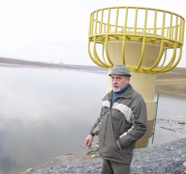 Jan Żłobicki, sołtys Włodzienina pokazuje nieczystości wylewane do zbiornika.