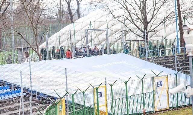 Hutnik Kraków - Znicz Pruszków. Kibice obserwujący mecz zza ogrodzenia stadionu
