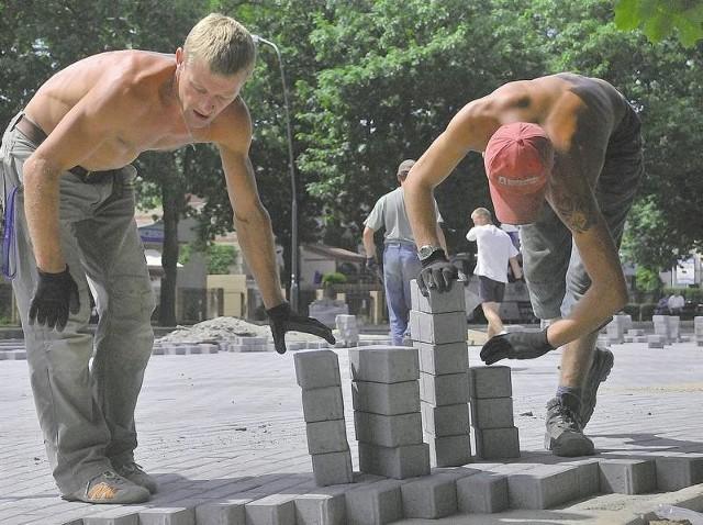 Maciej Wasiewicz i Paweł Dziuba układają kostkę brukową na parkingu. - Lada dzień skończymy prace. Pod koniec lipca będzie tu można parkować - mówią.