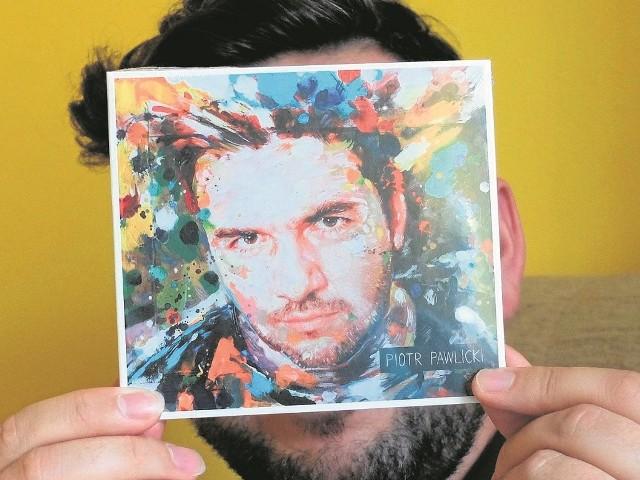 Piotr Pawlicki schowany za okładką swojej płyty. Można ją nabyć w Promocji Regionu Chojnickiego.