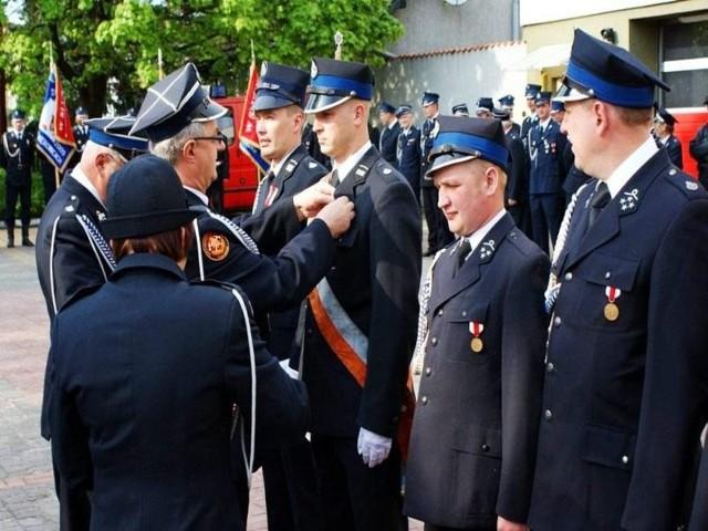 Robert Bobkowski otrzymuje srebrny medal za zasługi dla pożarnictwa. Wręcza mu go Marek Buza, prezes powiatowego zarządu OSP