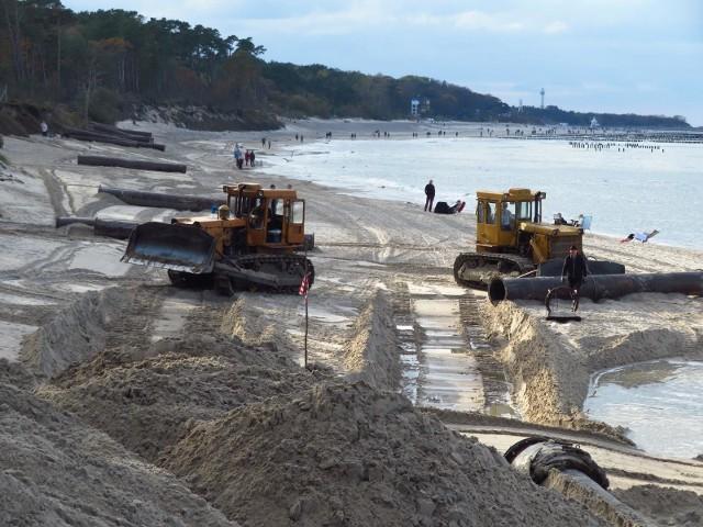 W Usteckim porcie pogłębiany jest tor podejścia oraz  oba zasobniki.  Wydobyty z nich refulat, czyli piasek i żwir zostanie złożony  na  231,100÷231,40 km plaży, czyli w okolicy ostatniego zejścia na plażę, przy ośrodku  Perła, naprzeciw  Osiedla Przewłoka.Sposób odłożenia refulatu na plaży to Minimalna długość zasilanego odcinka - 300 m. wysokość  półki:  3,0  metry,  minimalna  szerokość:  8-15,0  m  Przewidywalna ilość pisaku do wydobycia to 60 tys ton. TOR  PODEJŚCIOWY  Z  MORZA  PEŁNEGO do  punktu  położonego  w  odległości 1,2 kabla ( 220 m) od wejścia do portu,  długość:   926 m   szerokość w dnie:  60 m  głębokość: H T  = – 6,5 m  powierzchnia toru w dnie:  5,556 ha. OSADNIK PO STRONIE W: (zachodniej)  długość:    200 m  szerokość:  120 m  głębokość:  9,0 m   powierzchnia osadnika w dnie:  2,400 haOSADNIK PO STRONIE E: (wschodniej)  długość:   125 m   szerokość:  120 m  głębokość:   9,0 m   powierzchnia osadnika w dnie:  1,500 haZadaniem osadników na morzu, czyli zagłębienia w dnie morza, jest  przechwytywać wleczone po dnie  rumowisko  (piaski)  morskie.  Zadaniem  osadników  jest  przynajmniej  częściowe  przechwycenie  osadów  transportowanych  przez  fale  i  prądy  morskie  w  rejon  toru podejściowego i w ten sposób zmniejszenie tempa spłycania się toru.