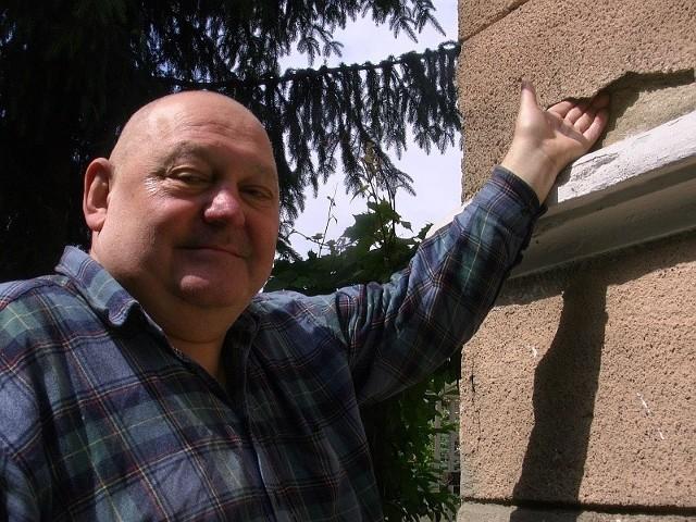 Janusz Mereżyński wkłada palce pod tynk na zabytkowej kamienicy, w której mieszka, by pokazać, w jakim stanie jest elewacja