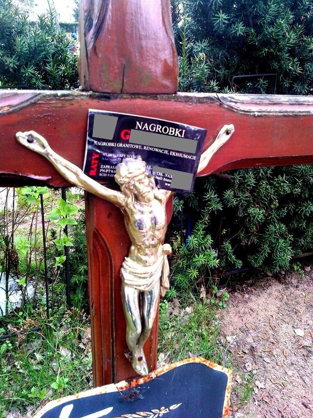 Reklamy na krzyżach nagrobnych. Zatknięte na postaciach Chrystusa