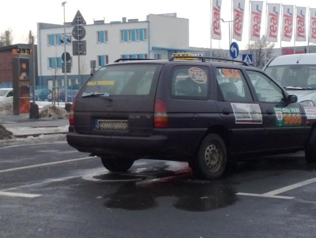 Taksówka zaparkowana na miejscu dla niepełnosprawnych.