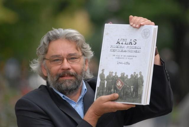 Bogdan Biegalski z atlasem historycznym, którego był współautorem