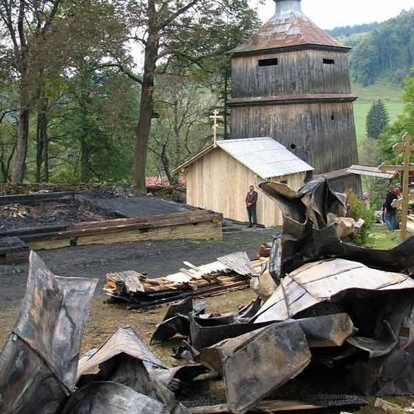 Tyle zostało po spalonej cerkwi w Komańczy. W tle: prowizoryczna kaplica i dzwonnica.