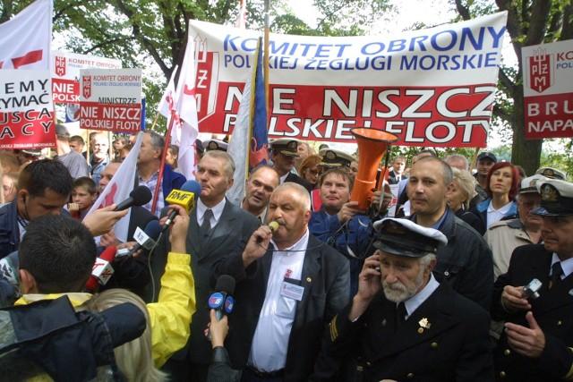 """Marynarze przeszli spod siedziby PŻM pod urząd wojewódzki. Na transparentach nieśli hasła """"Chcemy utrzymać miejsca pracy"""", """"Brutalna napaść na PŻM"""", """"Ministrze nie niszcz floty""""."""