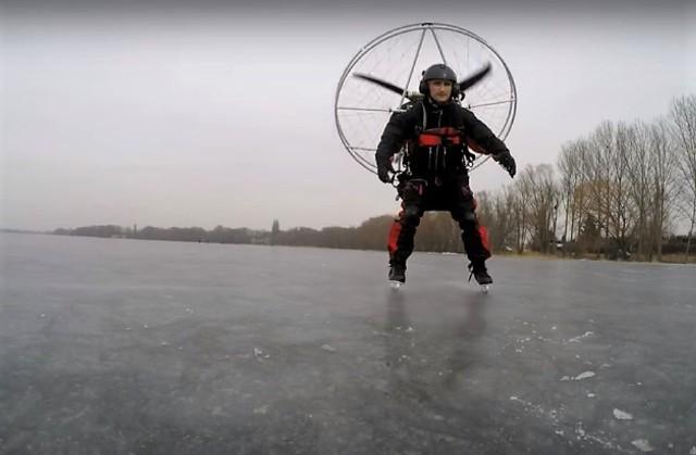 Robert Osiński w trakcie próby jazdy na łyżwach z napędem od motoparalotni na plecach
