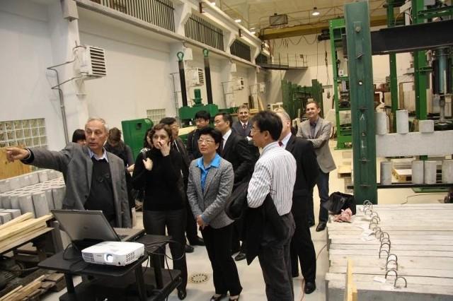 Profesor Wiesław Trąmpczyński z Politechniki Świętokrzyskiej pokazuje chińskiej delegacji laboratoria uczelni.