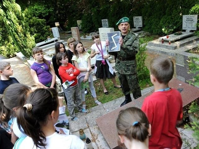 Dzieci z SP 61 nad mogiłą kapitana Konstantego Maciejewicza słuchają historii o znaku Rodła. Symbol Związku Polaków w Niemczech został stworzony w 1932 roku.
