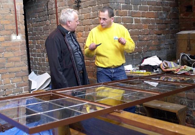 Dariusz Madejski, zajmujący się pracami na wysokości przygotowuje okna z witrażami do montażu w katedrze. Z lewej ks. Jan Kazieczko.