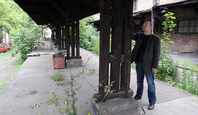 Marek Łuczak pokazuje zachowane do dziś zadaszenia historycznego dworca oraz widoczny po prawej stronie budynek, zamieniony przez PKP pod koniec jego powojennej historii na magazyn.