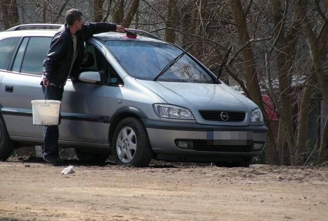 Kierowca mył swój samochód na drodze.