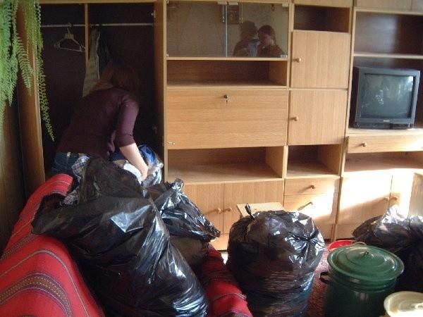Córka pani Marioli pakuje ubrania rodziców do  worków.