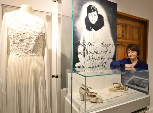 Marzena Bomanowska obok sukni i zdjęcia z autografem gwiazdy międzywojennego kina, Jadwigi Smosarskiej