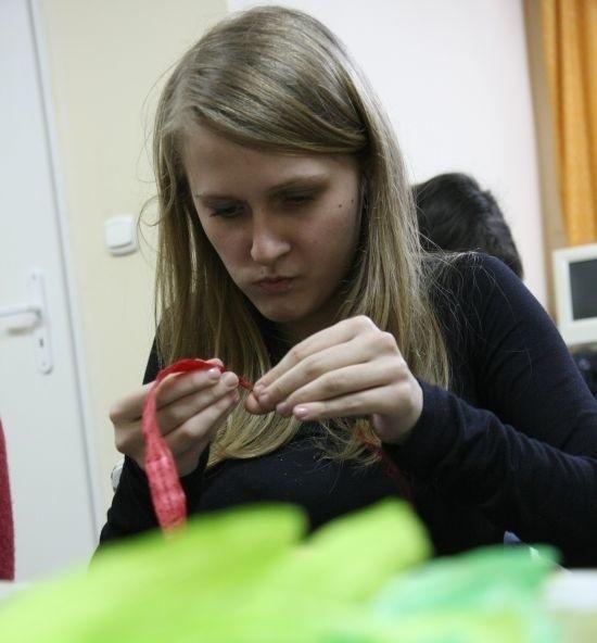 Anna Dolińska, wolontariuszka ze stowarzyszenia, tworzy ozdobne kwiaty ze specjalnego sznurka z bibuły