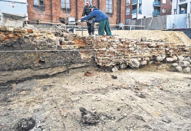 Teren wykopalisk. Na dole zdjęcia widać fragmenty drewnianych pali sprzed pół tysiąca lat, a u góry ścianę gruzowiska i ziemi, składającej się z warstw z zapisem  przeszłości Koszalina