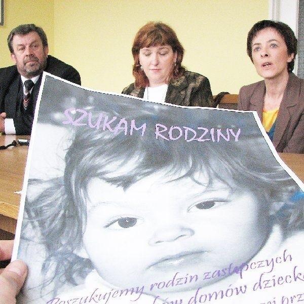 Na pierwszym planie plakat promujący ideę tworzenia rodzin  zastępczych, a na drugim - organizatorzy szkoleń z Ośrodka  Wspierania Dziecka i Rodziny (od lewej): dyr. Roman  Jaskólski oraz Małgorzata Strzemkowska i Anna Olejnik