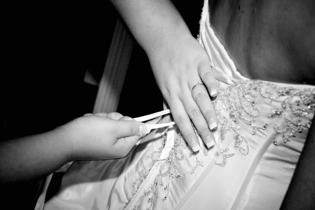 Świadkowa panny młodej m.in. pomaga w ząłożeniu sukni.