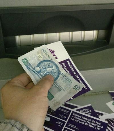 Bankomat Euronetu wydaje pieniądze i reklamowe ulotki.