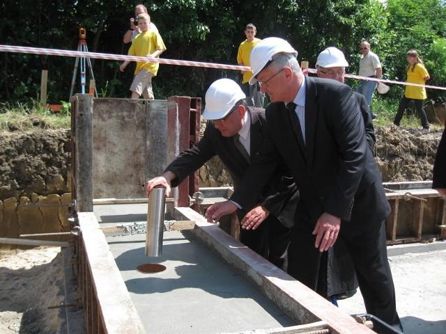 Burmistrz Roman Pogorzelec i starosta Marek Cieślak wmurowują akt erekcyjny i kamień węgielny