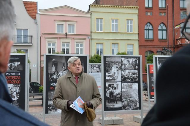 Zbigniew Reszkowski na tle wystawy na Starym Rynku.
