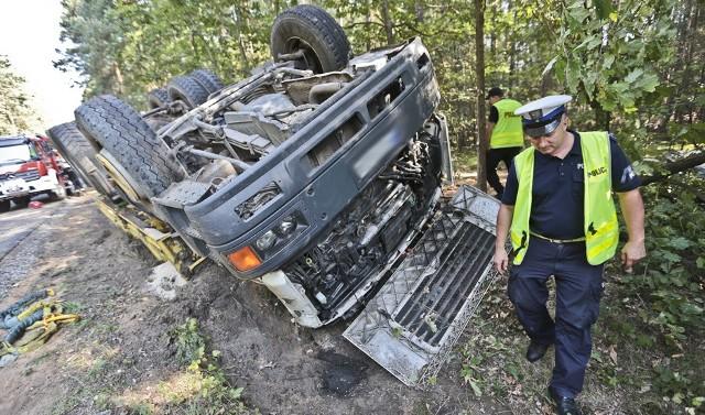 Do tragicznego wypadku doszło w piątek, 16 września, na trasie do Jarogniewic. Tir z piachem zjechał z wysokiego pobocza budowanej drogi, wpadł w poślizg, przewrócił się i zarył kabiną w ziemię. Mimo dramatycznej akcji ratunkowej kierowca nie przeżył.Ciężarówka z ładunkiem piachu jechała w kierunku Jarogniewic. Na prostym odcinku, tuż przed lekkim zakrętem kierowca ciężarówki najprawdopodobniej wpadł w poślizg. Wcześniej musiała zjechać z wysokiego pobocza wąskiej, nowobudowanej drogi. Samochód wypadł z drogi i dachował. Kabina zaryła mocno w ziemię.Pierwsi na miejsce wypadku dotarli zielonogórscy policjanci. Robili co mogli, aby dostać się do kierowcy w zmiażdżonego kabinie.  Pomagała im ekipa karetki pogotowia. Niestety ich wysiłki nie przyniosły skutku. Na miejsce jechali już wtedy wezwani strażacy ze specjalistycznym sprzętem.Ruszyła dramatyczna akcja ratunkowa. Strażacy hydraulicznymi nożycami rozcinali karoserię kabiny ciężarówki, żeby jak najszybciej dostać się do kierowcy, który nie dawał żadnych oznak życia. To było trudne zadanie, bo kabina była bardzo mocno zmiażdżona. W jej wnętrzu znajdował się uwięziony kierowca.Kiedy strażakom w końcu udało się dostać do kierowcy, medyk stwierdził jego zgon.Kierowcy, którzy zatrzymywali się w okolicach miejsca śmiertelnego wypadku winę zrzucali na wysokie pobocze budowanej drogi. – Żadnych znaków, żadnych ostrzeżeń, to ktoś odpowiedzialny z drogę powinien ponieść konsekwencje za śmierć kierowcy ciężarówki – mówili wszyscy zgodnie. Przeczytaj też: -   Śmiertelny wypadek na S3 w okolicy Sulechowa. Nie żyje kierowca forda i 12-letni chłopiec-   Kolejny wypadek na S3 pod Zieloną Górą. Dwie osoby w szpitalu [ZDJĘCIA CZYTELNIKÓW]