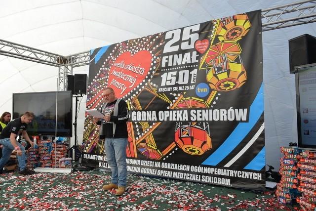 Jurek Owsiak przed plakatem finału WOŚP 2017.